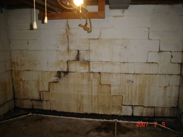 click for full size image a bowed basement wall with brown stains and